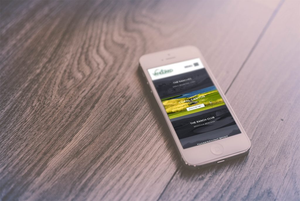 vanguard golf homepage on iphone 6, sitting on wood table
