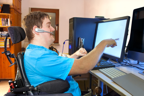 Young man in multifunctional wheelchair using a computer touchscreen, wearing headset