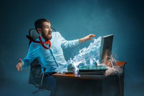 Man working at desk with email spam pouring out of computer screen